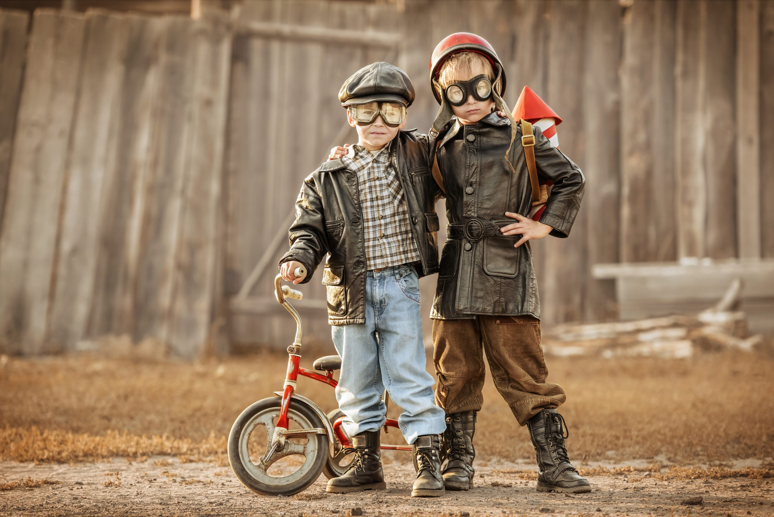 Boys in the image of a rider and a rocketman play in the backyard of the house
